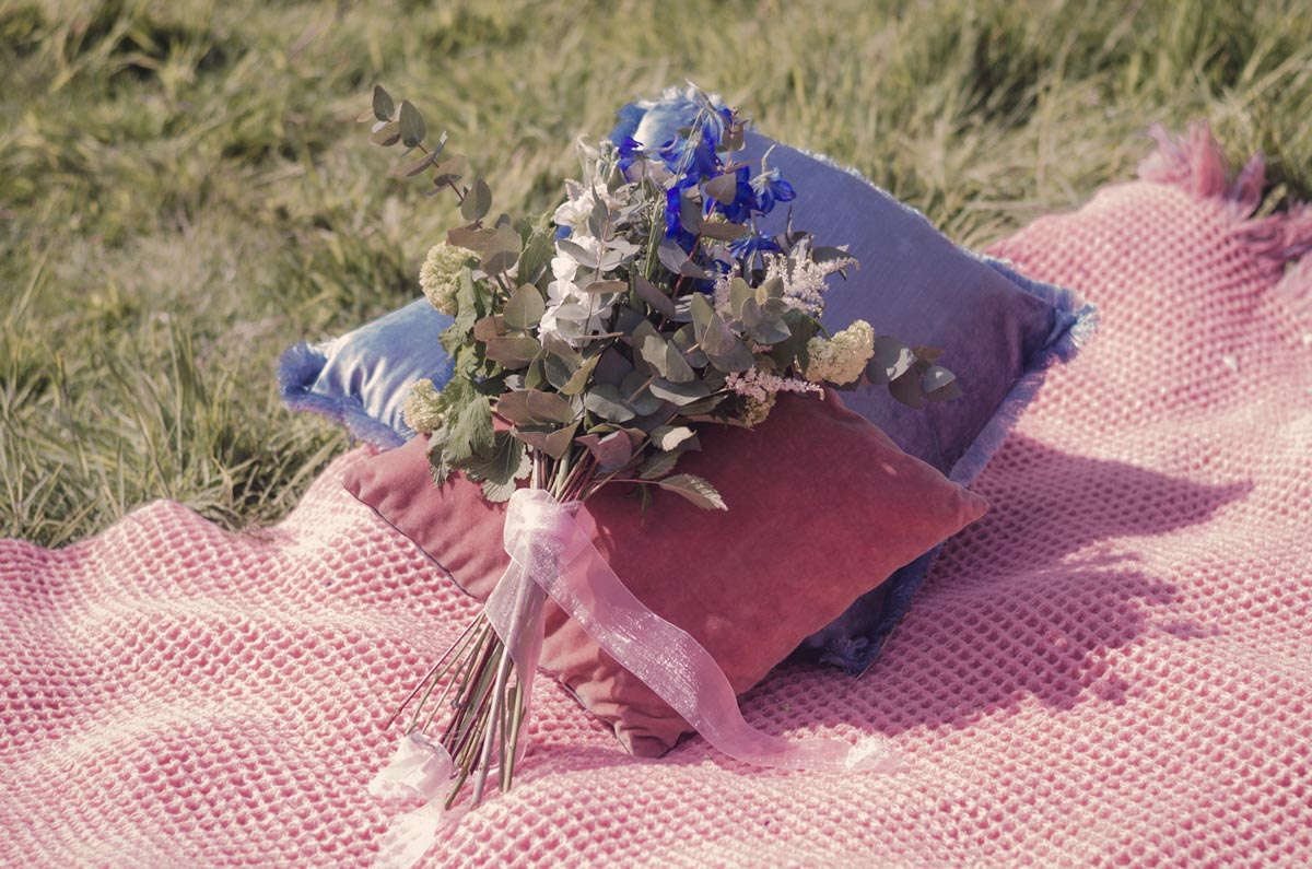 A bouquet of spring flowers upon the picnic blanket
