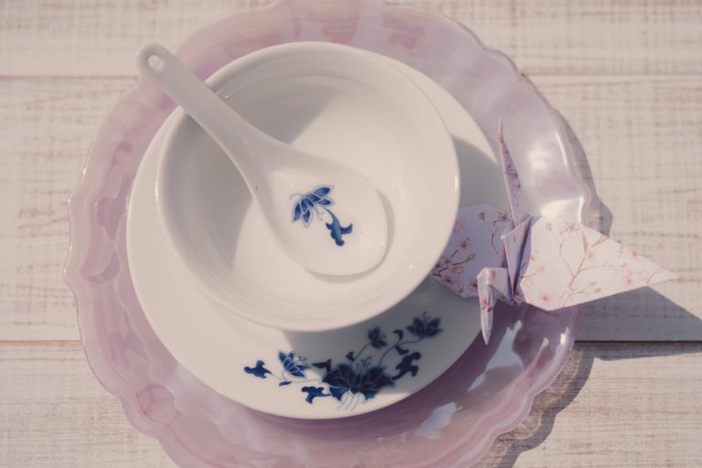 Origami bird placed upon oriental china plate with bowl and spoon