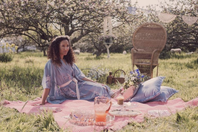 Out model reclines on a picnic blanket in the hazy sun