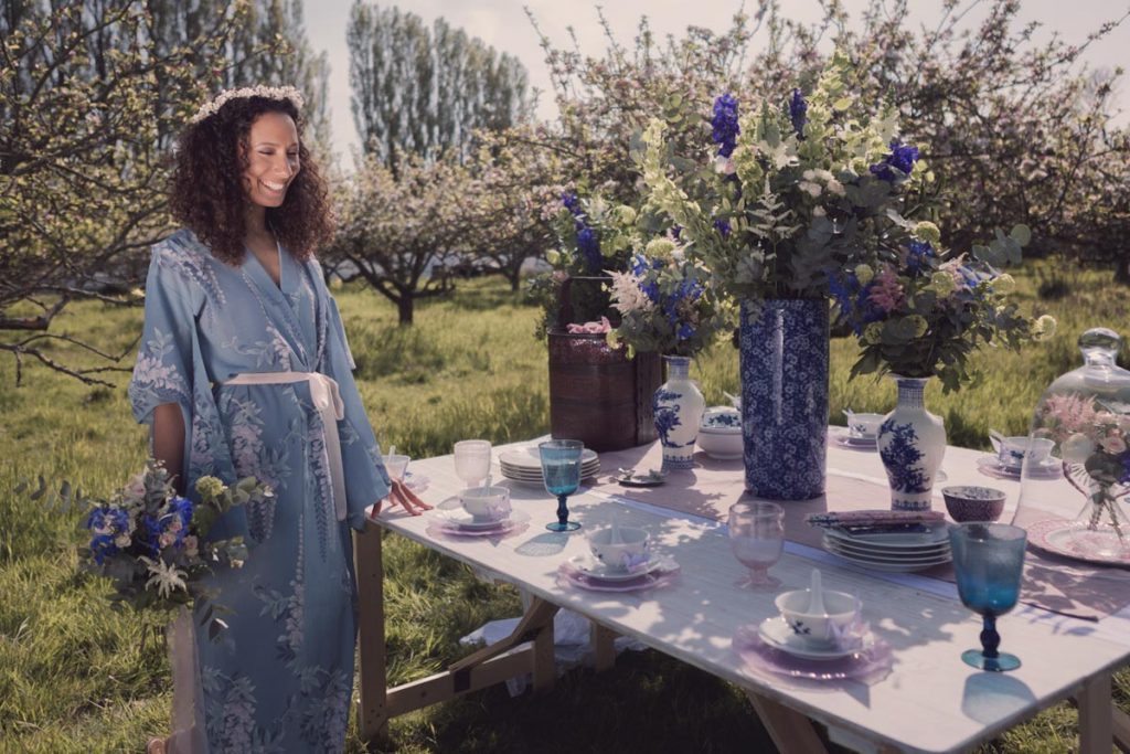Wearing a stunning smile our model wears a kimono standing close to a stunning oriental themed table spread