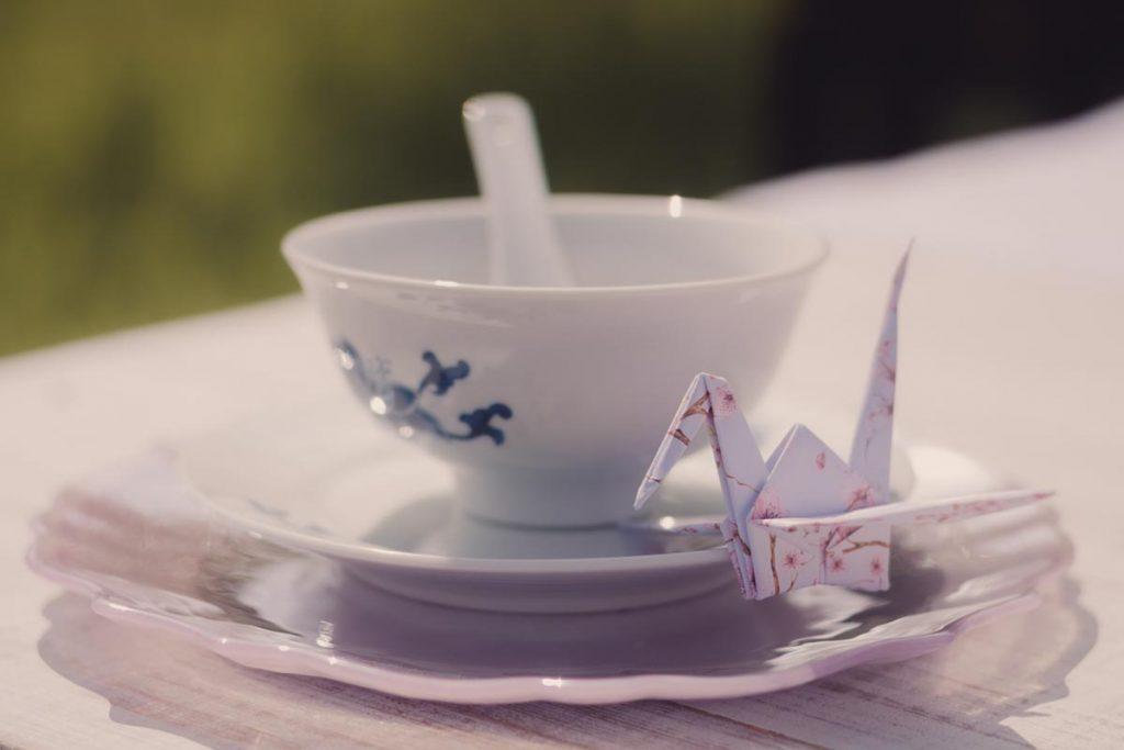 Delicate oriental style teacup with origami bird closeup
