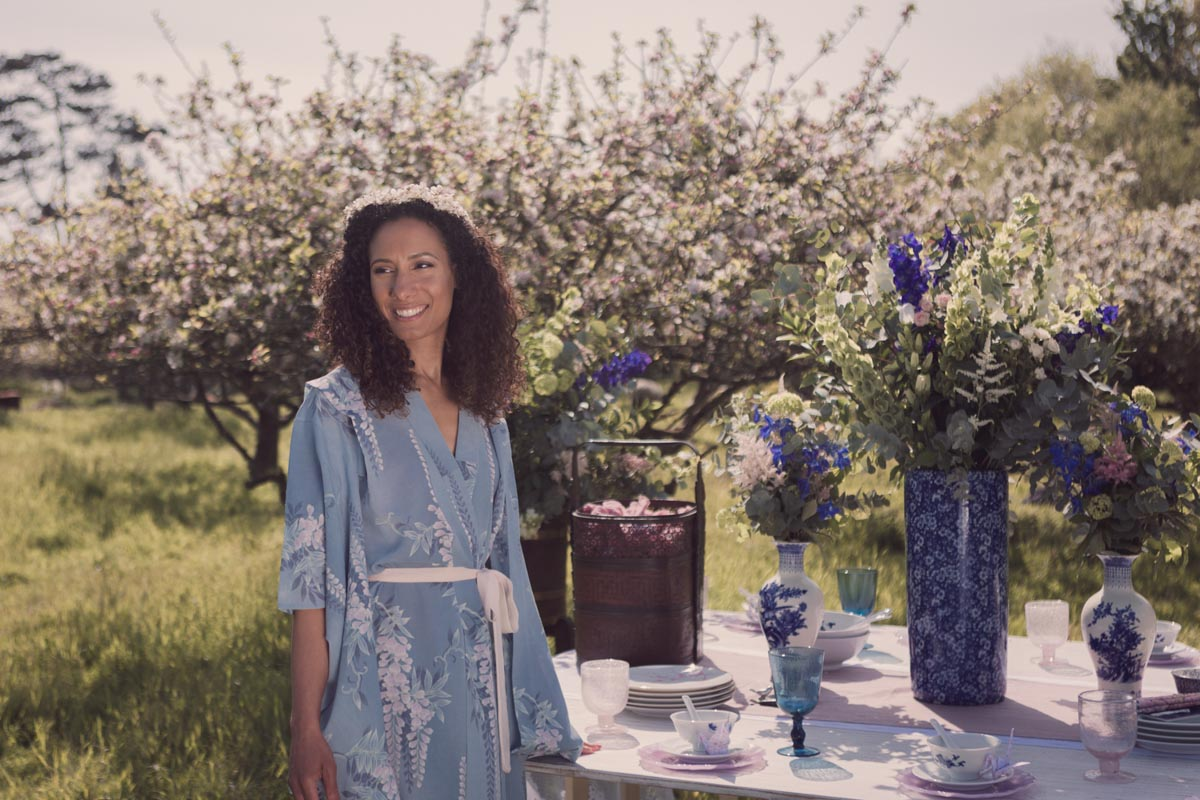 a model wearing a kimono standing close to a stunning oriental themed table spread