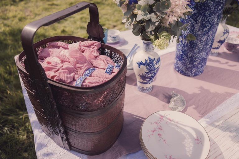 Rolled up napkins in a wicker basket placed on the decorative table spread