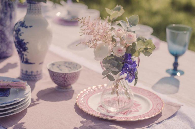 A delicate bouquet of flowers in a tear drop vase